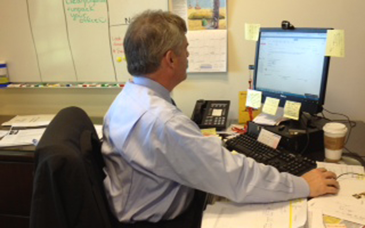 Carl Herrin smiles as he responds to emails in his office, 2013. Photo courtesy of Ni Lu